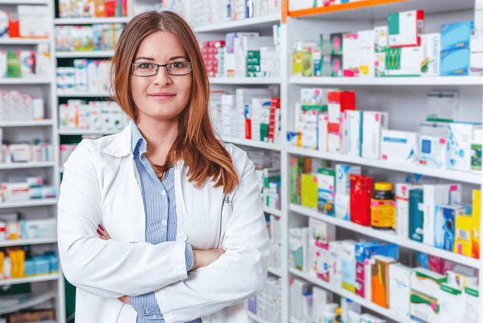 Pharmacist standing in front of shelves of medicine boxes and bottles