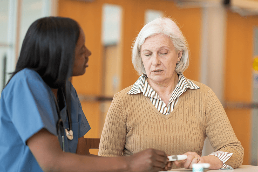 Medical professional talking to older woman at counter